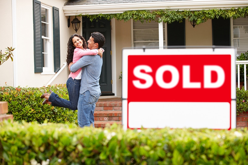 3 Reasons Why Your First Home Should Be An Investment Property couple in front of house smiling
