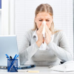 a business lady sneezing at her desk