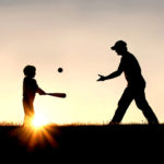 a dad teaching child to play ball