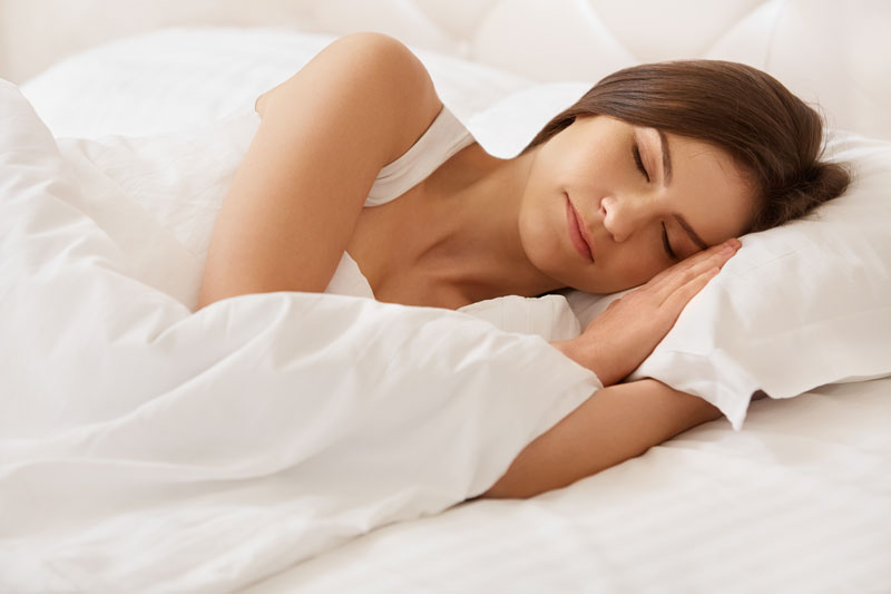 a woman sleeping in a white bed